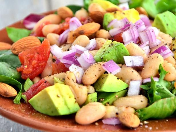 MEXICAN BEAN SALAD: 1 tablespoon extra-virgin olive oil 1 large red onion, diced 1 clove garlic, minced 1/4 teaspoon ground cumin 1/4 teaspoon sea salt 1/4 teaspoon freshly ground black pepper 2 (15 1/2 oz.) cans white beans 2 heads romaine lettuce, finely chopped 1/4 cup raw almonds, finely chopped 1 ripe avocado, diced 3/4 cup salsa 3/4 cup Greek plain yogurt