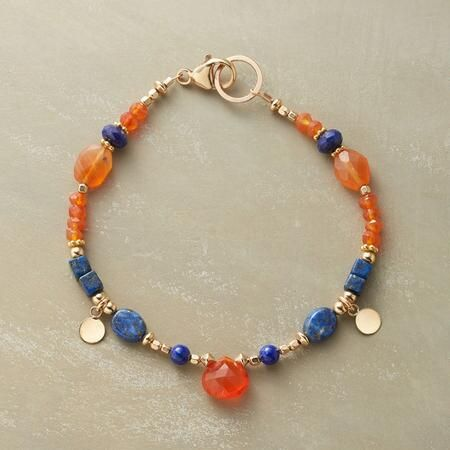 CIRCLE OF STONES BRACELET   A handmade carnelian and lapis bracelet that showcases bright orange carnelian and deep blue lapis in different shapes and sizes  accompanied by 14kt gold filled beads and dangling disk charms  Lobster clasp  Exclusive  Handcrafted in USA  Approx  7 1 2 quot L