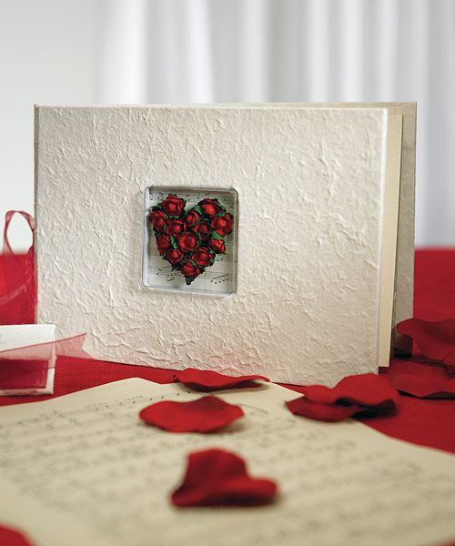 """Our Flower of Love In Romantic Red Guest Book is natural Mulberry paper covered and hand decorated with parchment roses in the shape of a heart, sits on a musical background. The perfect elegant touch for a music theme wedding! This guest book measures 9 1/2"""" x 6 1/2""""H and contains 20 white pages, which accommodates 530 names."""