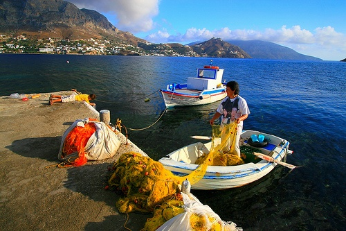 Harbour with fishing woman in her boat and yellow and orange fishing nets. Kalymnos view in the background. Telendos island , Dodecanese