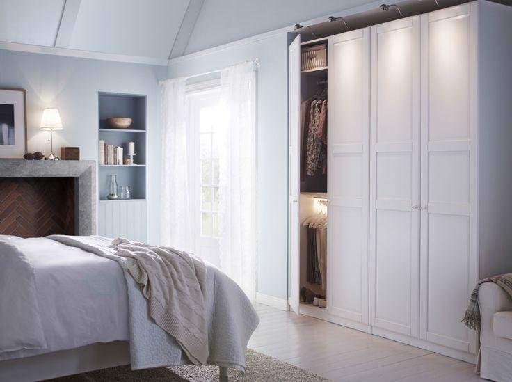 大きなワードローブと、ホワイトと花模様のベッドリネンを掛けたベッドを置いて、ホワイトでコーディネートしたベッドルーム。