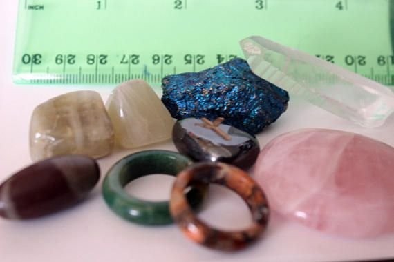 Ive put together this lot of gems and stones for the bohemian hearted crafter. You can make jewelry or other crafts and décor with these stones. I have chosen a gorgeous Peacock Ore, a powerful Quartz Point, A lovely Rose Quartz Palm Stone, a unique little Shiva Lingam stone, 2 Moonstones, a Hematite, Elhaz/Algiz rune, it is the symbol of protection, and two stone rings which has an INNER diameter of 18mms.  SIZE:* Actual crystals shown, please see photo for size as I have placed a ruler...