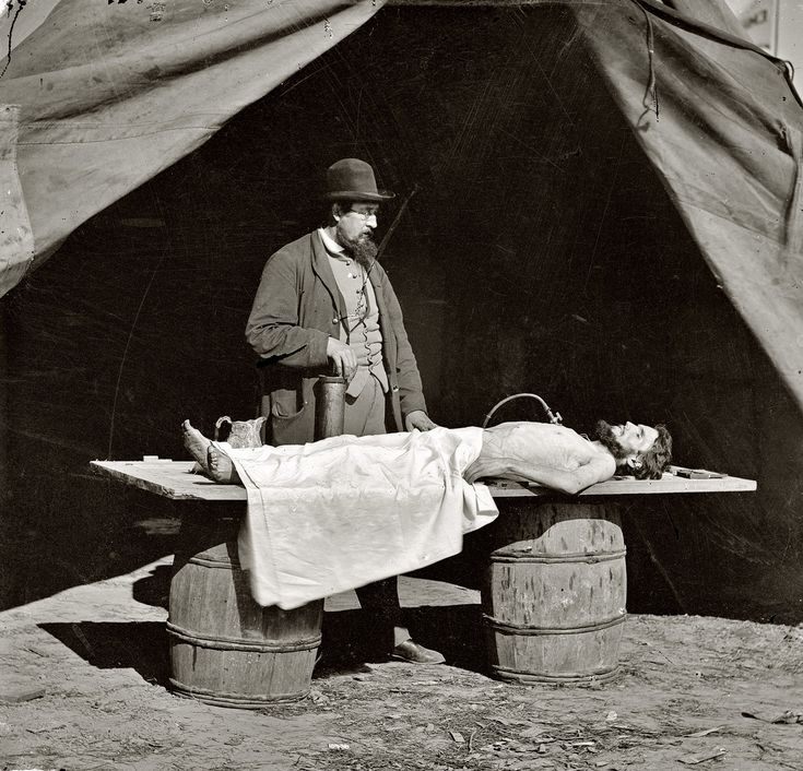 """Circa 1861-1865. """"Unknown location. Embalming surgeon at work on soldier's body. From photographs of artillery, place and date unknown."""""""