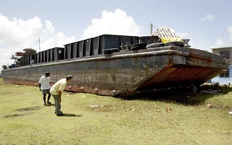 A ferry boat sits on a neighborhood in Isla de la Juventud, Cuba, after being tossed there by Hurricane Gustav