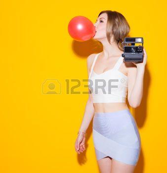 chewing gum: Moda in posa moderna in top colorato e gonna gonfia la bolla rossa da masticare su sfondo giallo in studio. Ragazze di modo di bellezza. Splendida donna del ritratto. Taglio di capelli alla moda e il trucco. Acconciatura. Trucco. Ragazza di fascino sexy sulla schiena Giallo