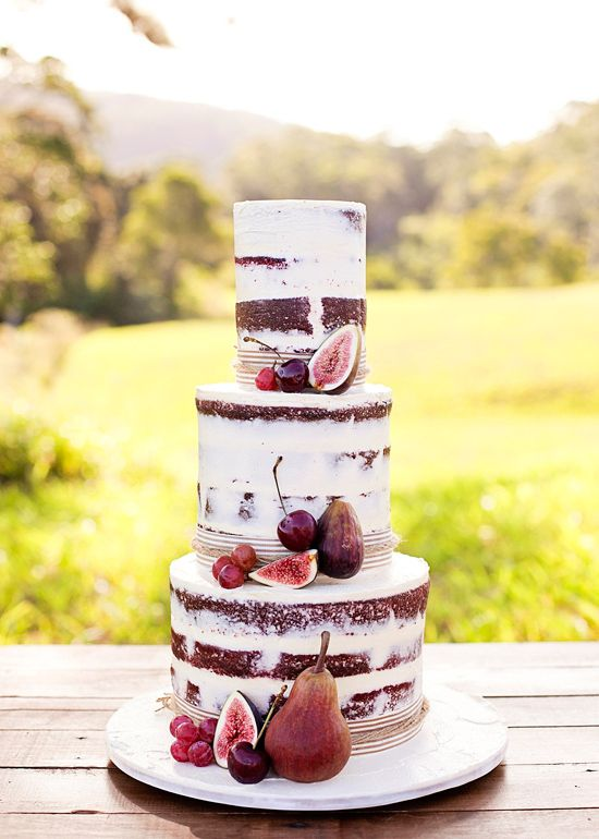 Red velvet wedding cake decorated with fresh fruit including Autumn plums, cherries, grapes and fresh figs.