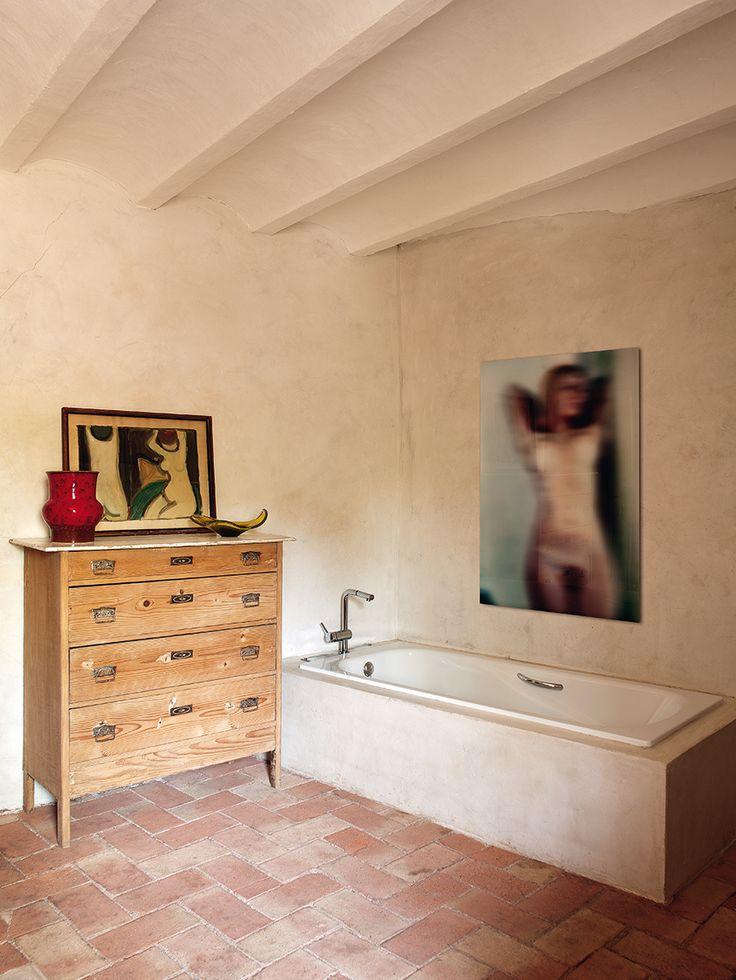 Spa rural - AD España, © Montse Garriga Bañera empotrada y cómoda de pino lavado sobre un suelo de barro cocido. El retrato desenfocado es de Juan Ramón Amondarain. Foto Montse Garriga Galerías relacionadas