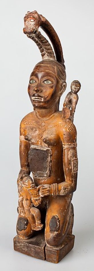 Figure: Kneeling Female with Serpents and Secondary Figures (Nkisi) Date: 19th century, inventoried 1885 Geography: Cabinda, Angola Culture: Kongo peoples; Vili group The torso of this kneeling female figure is a hollowed receptacle; the interior is exposed from the back, where a large rectangular panel is now missing. Once filled with consecrated matter by the priest who used it in his practice, it was likely deliberately emptied of that content before it was collected during an expedition…