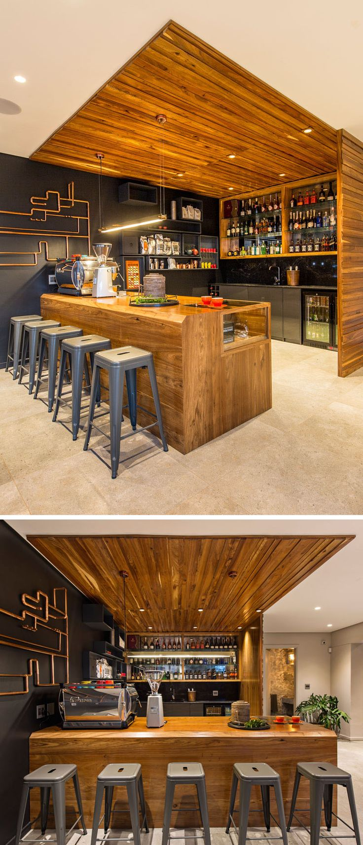 This modern wood bar has everything needed for making high quality coffee and cocktails. Black floating rectangular boxes blend in to the dark accent wall and provide additional storage.
