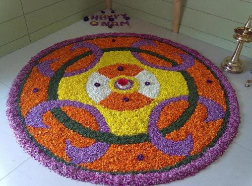 Onam Pookalam Designs with orange,yellow, white and purple colored flowers.