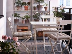 Balkon s bílými skládacími židlemi a stolem, police z galvanizované oceli