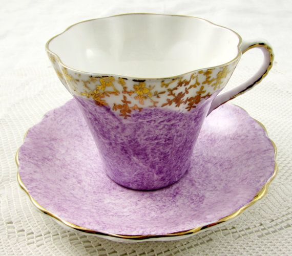 This beautiful bone china tea cup is from Sandringham. Rim of tea cup has a gold border. Both tea cup and saucer are purple. Gold trimming on cup and