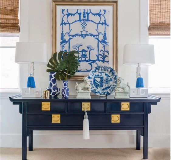 Trellis Home Design A lovely Chinoiserie vignette features Dana Gibson art, a pair of Greek key lamps, a pair of foo dogs, blue and white Chinese porcelain, and a Chinoiserie console table.