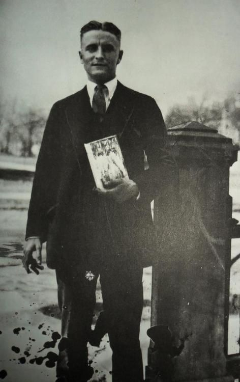 F. Scott Fitzgerald standing with a copy of The Great Gatsby. The Great Gatsby publication date: April 10, 1925