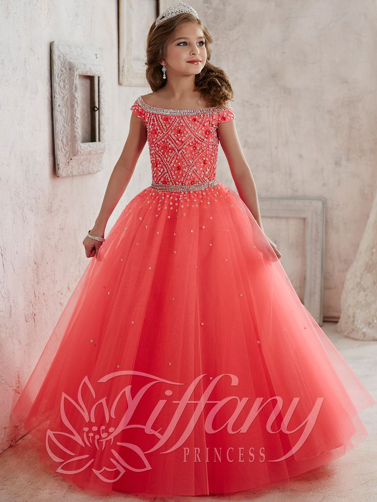 The judges will agree to make her the queen when she performs in this dreamy pageant dress from Tiffany Princess 13458. Exquisite crystals trim the off the shoulder neckline as well as the natural waistline. The bodice is decorated with an intricate beaded pattern as scattered sequins shimmer over the full tulle skirt for a lavish feeling. Lace-up back. Features:  Silhouette: A-Line Ball Gown  Neckline: Off The Shoulder  Fabric: Tulle/Beaded/Crystals Sizes Available: 0 through 16   Colors…