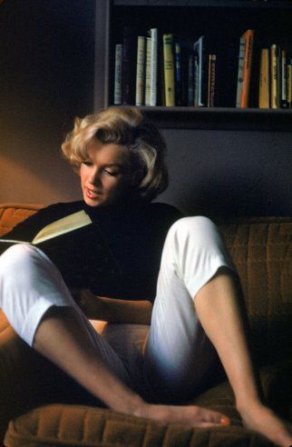 Marilyn Monroe curled up with a book at her Hollywood home in 1953