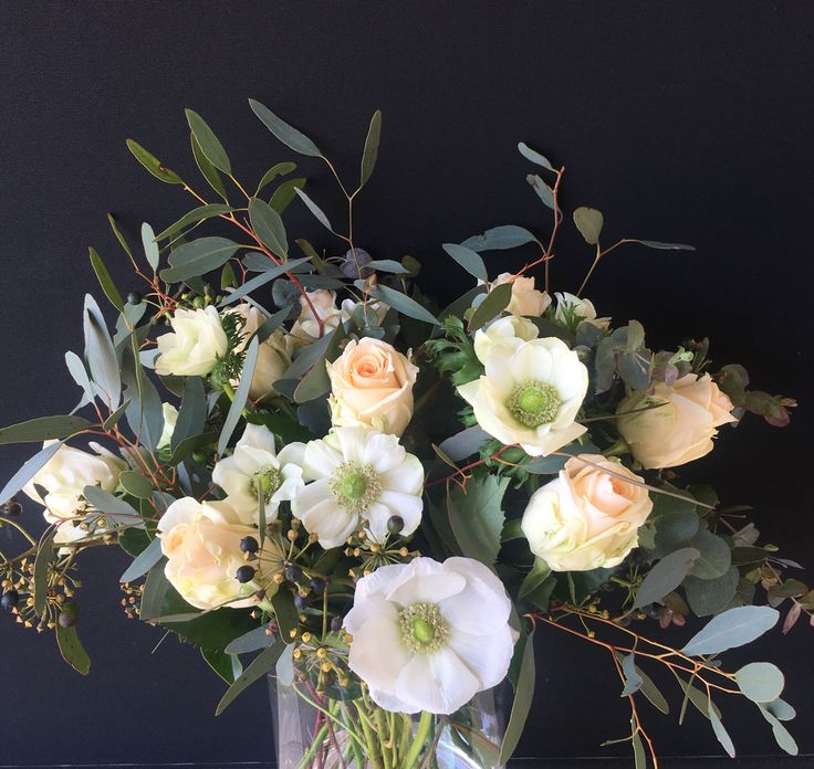 Table centerpiece vase arrangement by Bettie bee blooms. Blue gum, white anemone, peach roses.