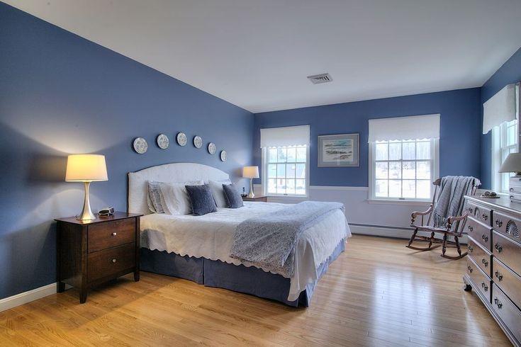 Blaue Wände an weißen getrimmte Masterbedroom kreieren einen eleganten Look und machen die weißen gerahmte Fenster und obenliegende Display pop.