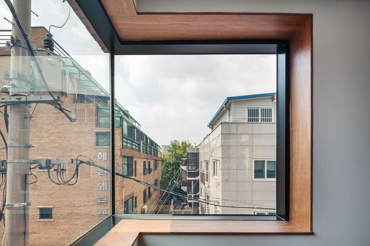 A circulation space leading to a roof terrace with separate entrances for people and cats connects split levels inside this tall and narrow house in Seoul.