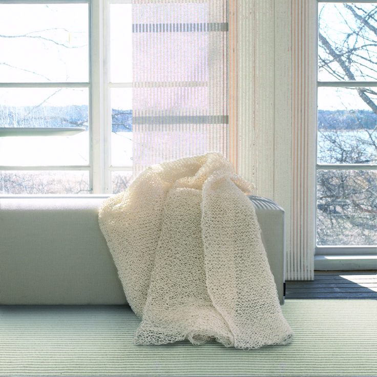 Woodnotes bench upholstered with Sand paper yarn cotton fabric and hand knitted paper yarn Seaborn throw.