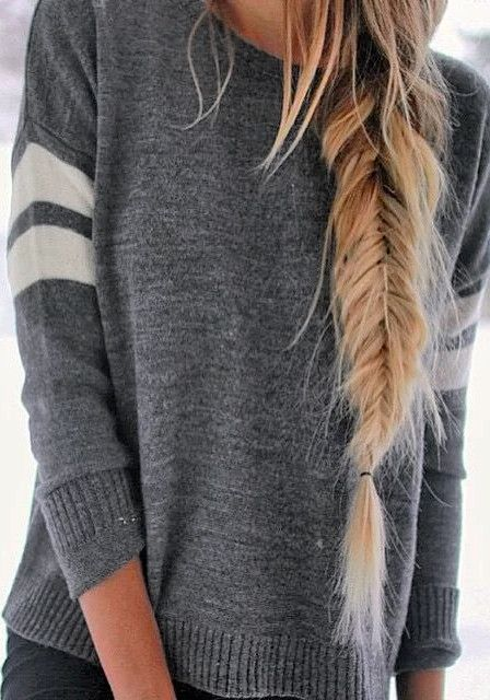 »Girl in classic grey knit sweater sporting side fishtail hairstyle«