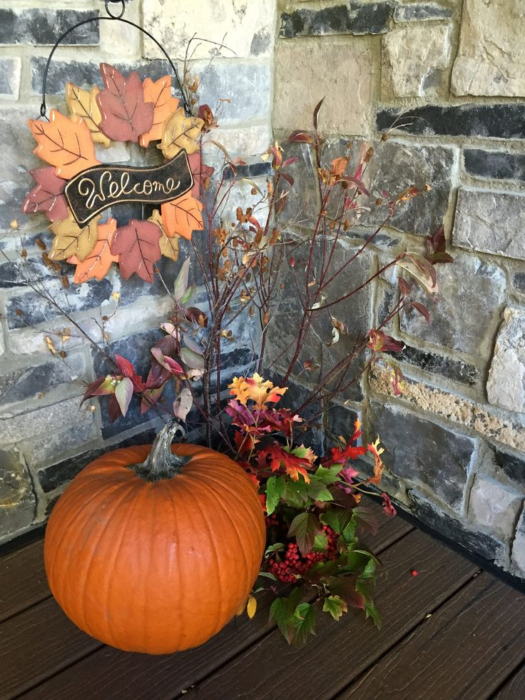 Autumn outdoor decor with real pumpkin, leaves and a welcome sign