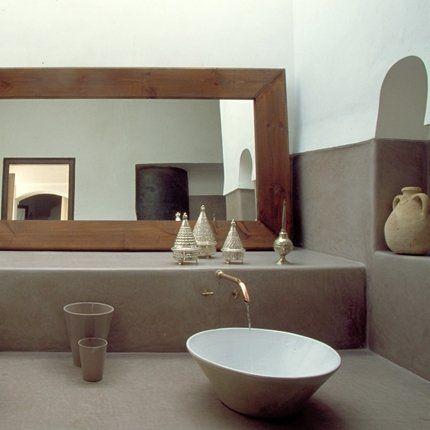 La salle de bains avec robinetterie de cuivre  Sur la desserte de la salle de bains, un miroir s'étend comme une fenêtre sur toute la largeur du mur, diffusant une lumineuse sobriété. La robinetterie de cuivre, simple et raffinée, surplombe deux vasques en céramique qui semblent posées sur la paillasse. Là encore, les murs ont été enduits de tadelakt. Poteries anciennes et boîtes en cuivre argenté (Trésor des Nomades).