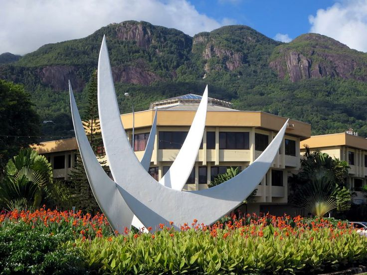 Trois Freres Peak (699 meters) provides a backdrop for the Statue of Three Continents in Victoria, Seychelles.