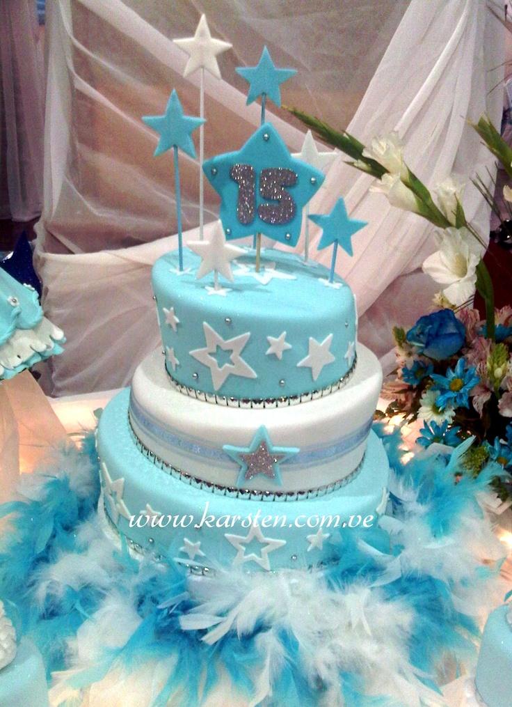 Torta de 15años inclinada en color Azul Cielo y Blanco decorada con estrellas hechas en pastillaje y pequeños detalles en color plata. Con una base adorna con una boa de plumas color Azul y Blanca