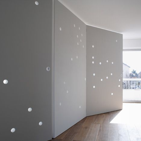 beautiful room dividerconcept for dividing an interior. Featured on DEZEEN, Light glows through the circular holes to give a star-studded appearance to the walls, which were designed by French studio Cut Architectures. Photography is by David Foessel.