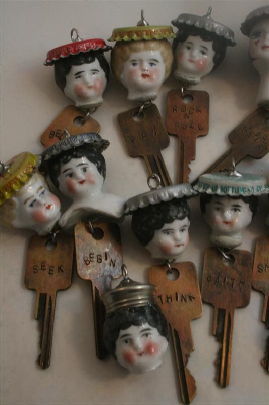 """Charlotte Keys someone made for etsy sale """"...Charlotte doll heads (made of porcelain and dating from the 1800's), I've added a hand stamped key, that says """"Faith"""". For her hat, she wears a vintage """"Hires"""" bottle cap. Each doll pendant has her own word. no two word were repeated. she will come on a ball chain and measure 24""""."""""""