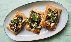 Three rectangular aubergine, basil and feta tarts lined up at an angle on an oval plate