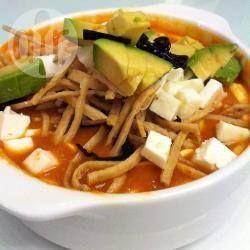 Mexikanische Tortillasuppe - Tortillas werden in Streifen geschnitten und frittiert und dann in einer tomatigen Hähnerbrühe serviert. Für eine authentische mexikanische Suppe mit Avocado, mexikanischem Käse und Crema servieren. @ de.allrecipes.com