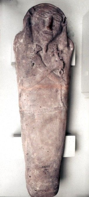 Base and lid of a red pottery coffin: pseudo-anthropomorphic, the face and hands modelled in relief. One hand holds a cruciform symbol, apparently fastened to a chain around the waist. This evidence has been used to suggest that the deceased was a Christian, containing the mummy of a small child, sex uncertain, wrapped in interwoven linen bandages with a fringe around the head. A compact sandy material, possibly a form of coarse plaster, holds the body in its coffin.