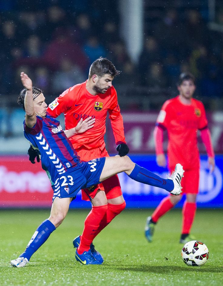 Gerard Pique of FC Barcelona duels for the ball with Javier Lara of SD Eibar during the La Liga match between SD Eibar and FC Barcelona at Ipurua Municipal Stadium on March 14, 2015 in Eibar, Spain.