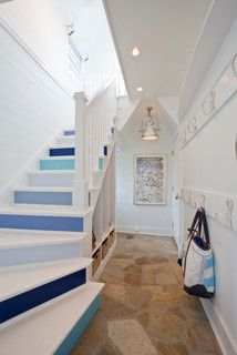Painted stair risers by Erin Paige Pitts Interiors, different shades of blue on the risers. The white rope hooks great for a beach house.