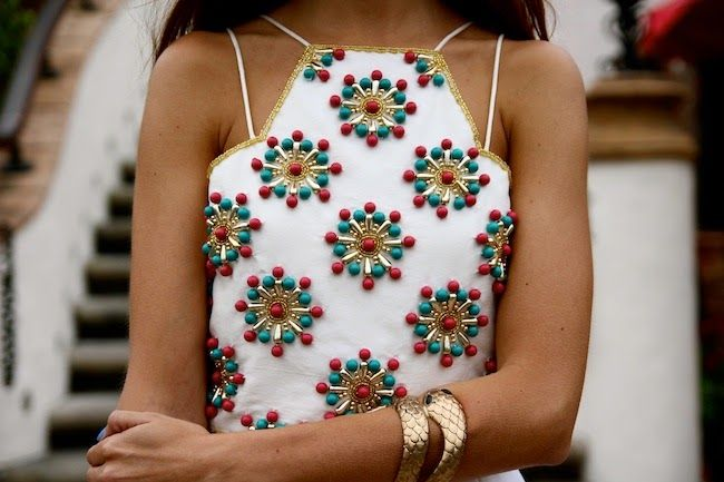 Sun star beading on a white blouse with delicate straps to balance the heavy embellishment