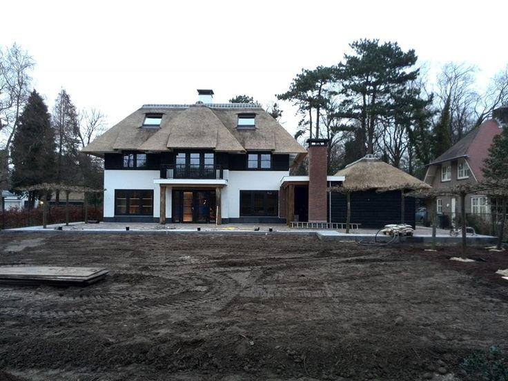 gestuct huis met zwarte potdeksel planken. Rieten dak vanaf de tweede verdieping met plat dak. Achterkant.