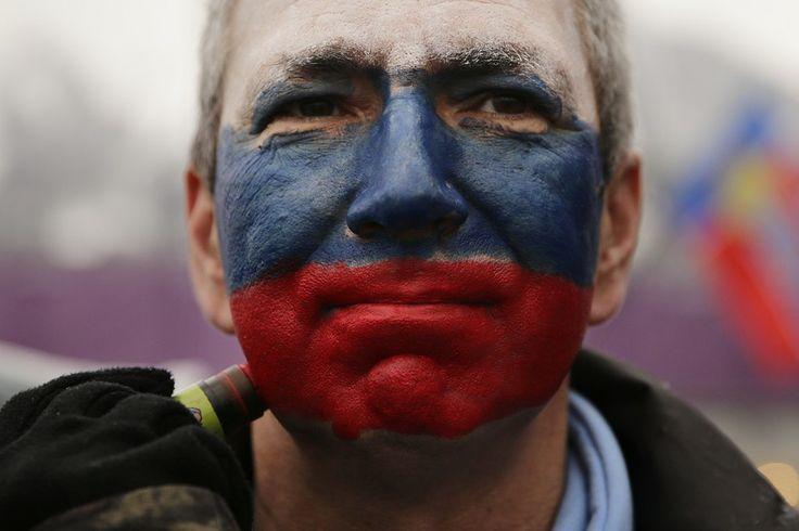 Torcedor pinta o rosto com as cores da bandeira da Rússia para assistir à prova de esqui feminino desta sexta-feira (21) nos Jogos Olímpicos de Inverno de 2014, realizados em Sochi - http://epoca.globo.com/tempo/fotos/2014/02/fotos-do-dia-21-de-fevereiro-de-2014.html (Foto: AP Photo/Jae C. Hong)