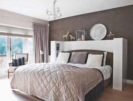 De slaapkamer is een oase van rust door het gebruik van zachte aarde- en kiezeltinten. Het deken, de kussens en de witte kroonluchter zijn van Riverdale. Het dekbedovertrek is van Zara.