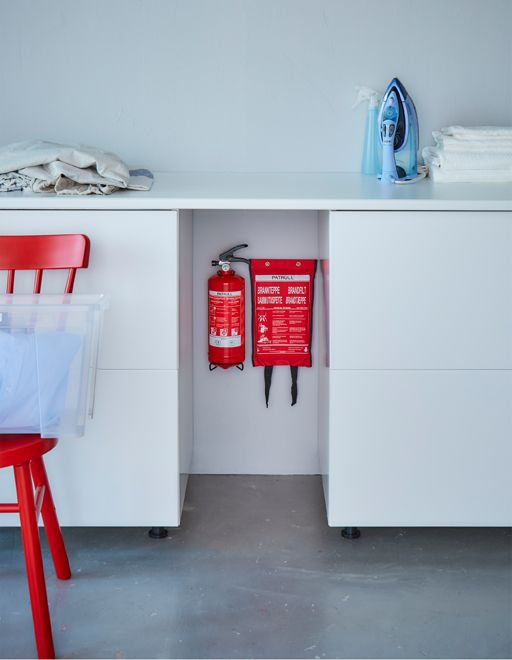 A fire extinguisher and fire blanket are hung on a wall between two cabinets.