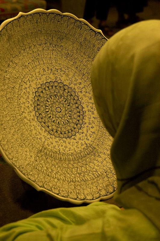 A woman looking at the ceramic plate