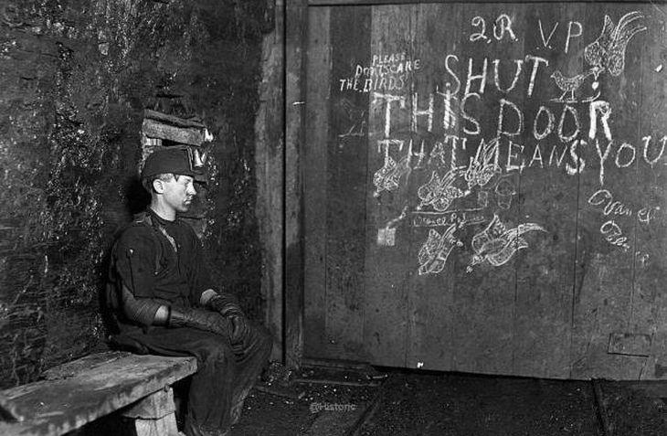 Um garoto de 15 anos de idade, sentado em uma porta para a entrada de uma mina de carvão na Virgínia Ocidental, em 1908. Esses meninos eram pagos uma miséria para sentar-se no mesmo local por 10 horas, para abrir e fechar as portas de hora em hora quando o carro de carvão estivesse chegando e saindo.
