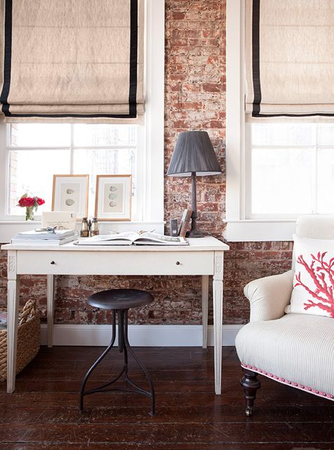 An exposed brick wall, a popping pillow, a rustic desk, large windows, fun window treatments. I'm there.
