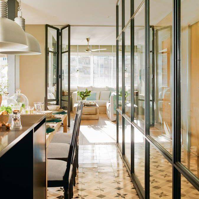 Cocina vista con pared de cristal con perfilería y puertas plegables, suelo de baldosas hidráulicas, barra y lámparas de aire industrial.