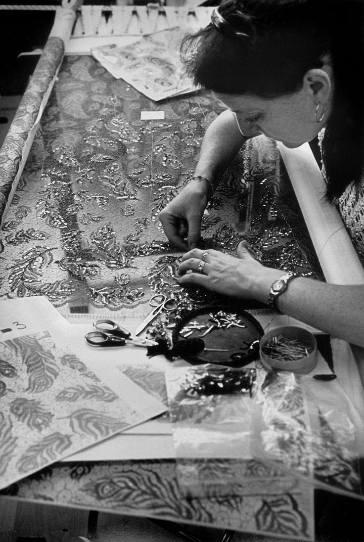 A women sews embellishment on lace for Chanel haute couture.  photographed by Ferdinando Scianna