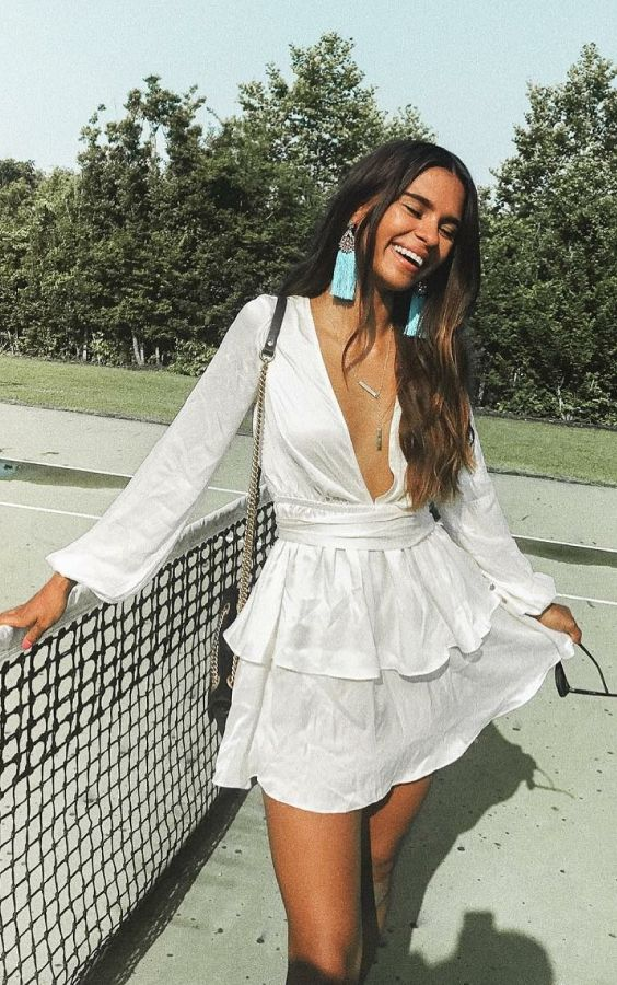 6 ideias de vestidos para você começar a pensar na primavera. Vestido branco de manga com babados e decote profunco, brinco de franjinhas azul