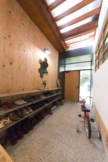 2階からの光が差し込む明るく広々とした洗い出しの玄関には、スチールの棚受けと足場板で下足棚を作った。