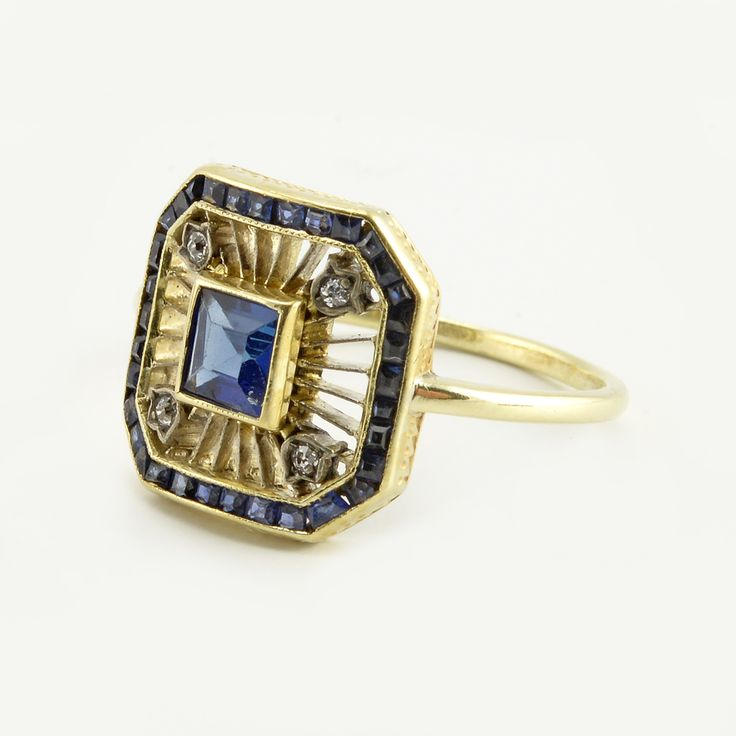 A rare Fabergé sapphire, diamond, and gold ring, Moscow, 1908-1917. The plaque centered with a princess cut sapphire within a sunburst pattern of gold applied with diamond-set lilies-of-the-valley at the corners, all within a border of calibre cut sapphires. In original Fabergé fitted case of holly wood with silk- and velvet-lined interior.