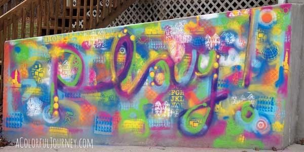 Mixed Media Painting on outdoor concrete wall with temporary chalk paint by Carolyn Dube using StencilGirl stencils.